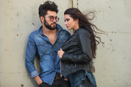young casual couple posing outdoor, in the wind; the man is holding his hands in his pockets and looking at the woman while she is holding her jacket and looking away photo