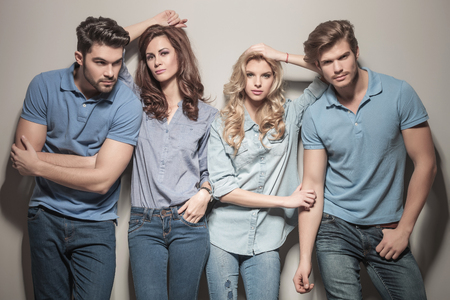 women leaning against their handsome men . two couples of young casual people standing together in studio photo