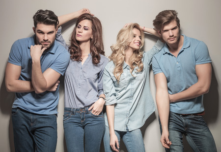 two couples of young casual fashion people posing for the camera, women looking at their men photo