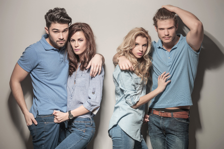 women embracing their boyfriends while posing in studio, dressed in casual jeans clothes photo