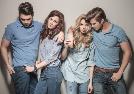 women in jeans: men and women standing together in casual jeans clothes , posing for the camera