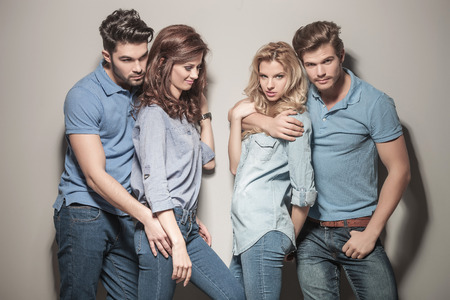 man in jeans: two young couples of casual people standing embraced near each other
