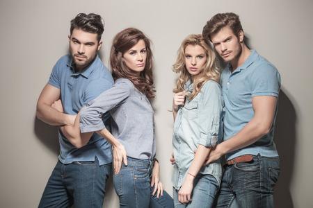 modelos hombres: modelos de moda en pantalones vaqueros y camisas de polo ocasionales que presentan en estudio Foto de archivo