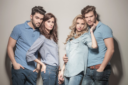 relaxed casual group of young fashion friends standing together against gray studio wall photo