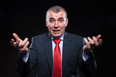 mature businessman: shocked old business man gesturing in confusion, at his desk in studio Stock Photo