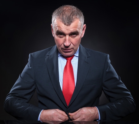 mature businessman: seated old business man is buttoning his suits coat at his desk Stock Photo