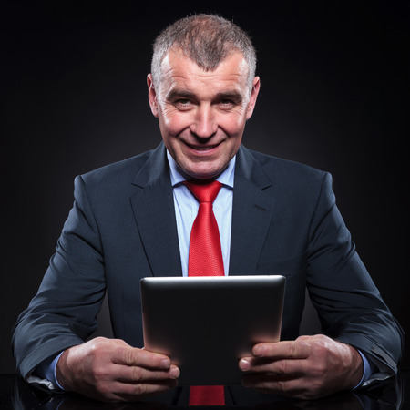 smiling old business man working on his tablet pad computer at his office desk Stock Photo