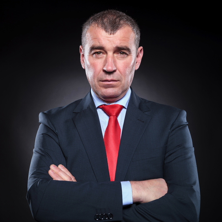 angry businessman: serious mature business man looking at the camera with hands folded on black background