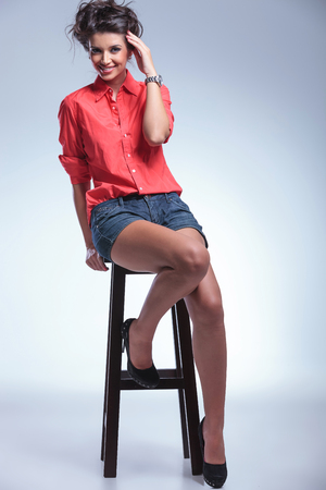full length picture of a seated casual young woman touching her head while looking into the camera. on gray studio backgroud