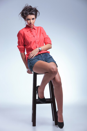 high chair: full length photo of a casual young woman sitting on a high chair and looking into the camera. on gray studio backgroud Stock Photo