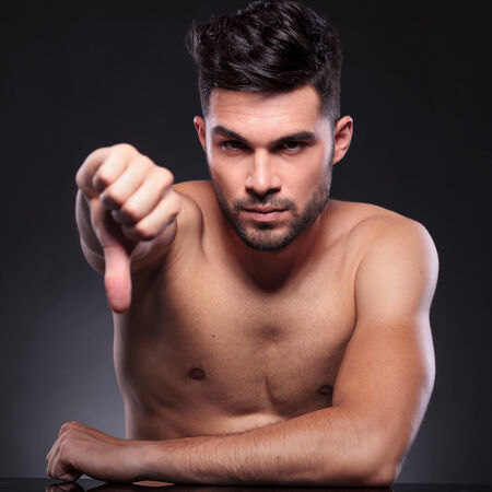 thumb down: young man sitting at his desk and showing the thumbs down gesture while looking at the camera with a serious expression on a black studio background