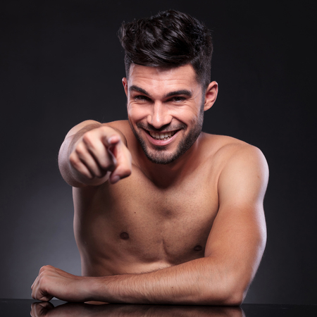 nackte brust: junger Mann sitzt an seinem Schreibtisch und zeigt auf die Kamera, während lächelnd auf schwarzem Hintergrund Studio Lizenzfreie Bilder