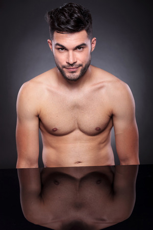 nackte brust: Porträt eines jungen Mannes mit einem nackten Oberkörper an seinem Schreibtisch und schaut in die Kamera auf schwarzem Hintergrund Studio