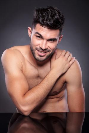 nackte brust: Junger Mann mit einer nackten Brust sitzt am Schreibtisch mit seiner Hand auf seine Schulter, w�hrend andere in die Kamera schaut und l�chelnd auf einem schwarzen Studio-Hintergrund