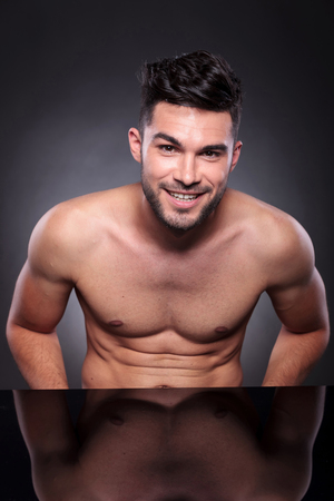 young man with bare chest smiling for the camera on a black studio background photo
