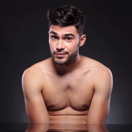 nackte brust: Junger Mann mit einer nackten Brust in die Kamera schaut mit hochgezogenen Augenbrauen beim Sitzen am Schreibtisch auf schwarzem Hintergrund Studio