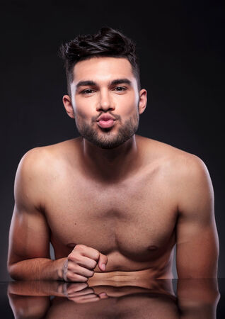 anticipating: young man preparing to kiss on a black studio background
