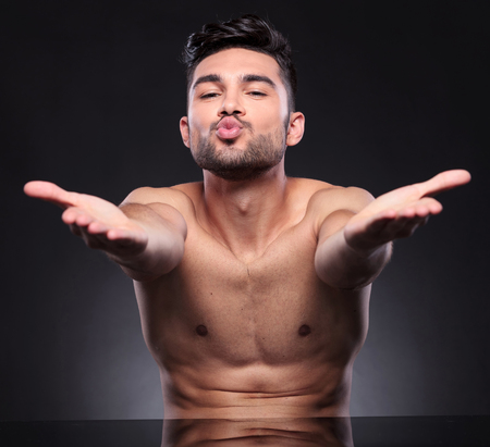 hot boy: young man blowing kisses with both hands while looking into the camera on a black studio background