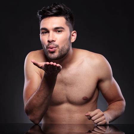 beso labios: joven detrás de un escritorio que está enviando un beso en el aire sobre un fondo negro del estudio