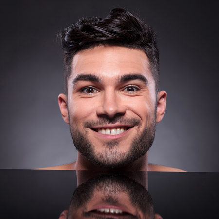 smug: close-up of the head of a young man looking into the camera with a smug smile on his face. on a black studio background
