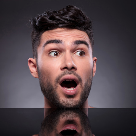 mouth opened: closeup of the head of a young man looking away surprised, with his mouth opened on a black studio background