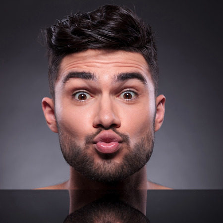 hot kiss: closeup of the head of a young man preparing to kiss you on a black studio background Stock Photo