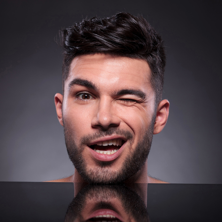 closeup of the head of a young man winking to the camera. on a black studio backgroud Stock Photo