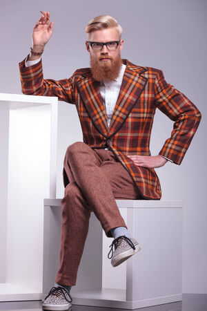 relaxed fashion man with long beard is sitting and smoking a cigarette, looking at the camera photo