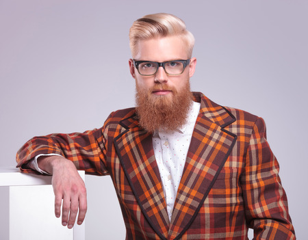 fashion man with long red beard and glasses resting in studio looking at the camera photo