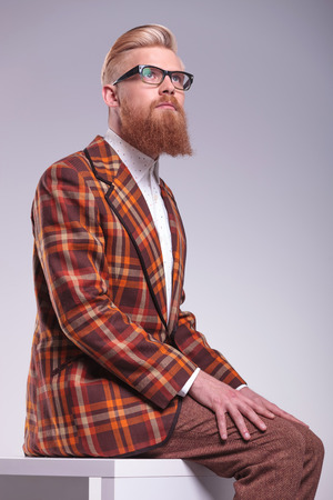 relaxed male model with long beard and glasses looking up to his side photo