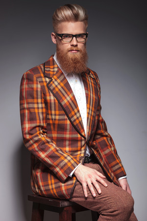 serious fashion man with long beard and great hairstyle sitting on a chair and looks at the camera photo