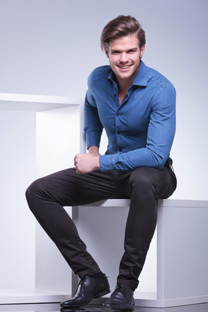 young casual man in shirt and pants is sitting and smiles for the camera, studio shot photo