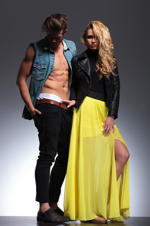 woman pulling by her boyfriend's pants while posing together as a sexy fashion couple photo