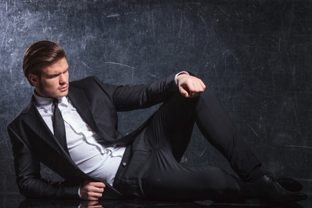 fashion elegant man in black suit and tie lies down and looks away from the camera in studio photo