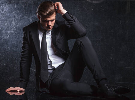 full suit: seated elegant fashion man is looking thoughtful and sad while lying down on studio floor