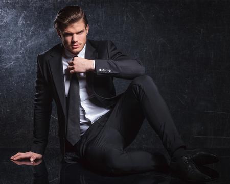 hombre sentado: sentado el hombre de moda elegante provocadora es la fijación de su corbata negro en estudio