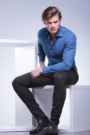 cool fashion casual man sitting on a cube and looks at the camera photo