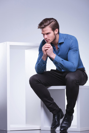 side view of a pensive young casual man looking away from the camera photo