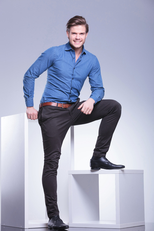 full body picture of a relaxed smiling casual man standing with leg on a cube photo