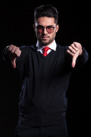 young business man wearing a pullover shows both thumbs down while looking into the camera. on a black background photo