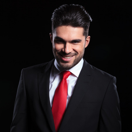 smug: young business man looking into the camera with an evil smile on his face. on a black background