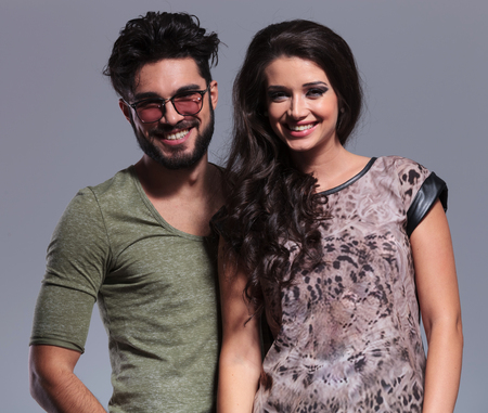 happy young casual couple laughing together for the camera, studio portrait photo