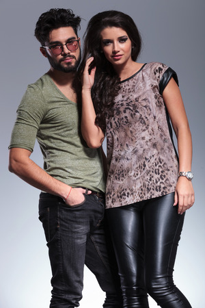young couple posing for the camera in studio, man with hands in pockets photo