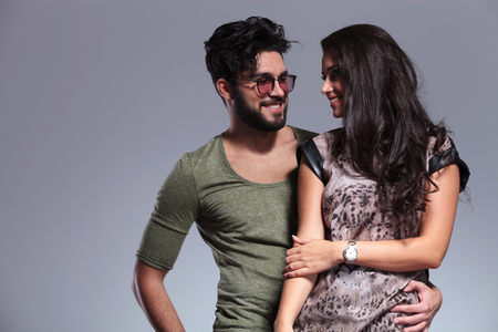 young casual couple smiling to each other and standing embraced in studio photo