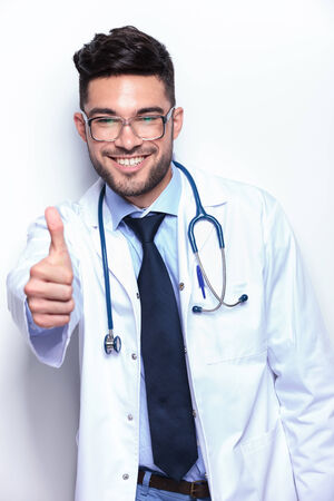 portrait of a young male doctor showing the thumb up sign to the camera while smiling. Stock Photo - 27109024