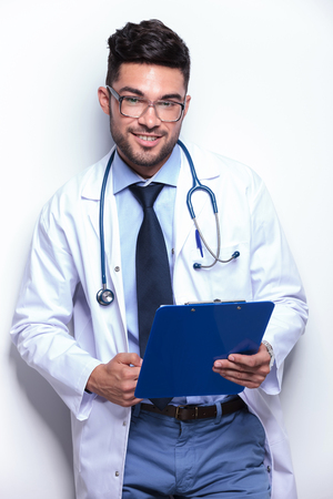 young male doctor smiles for the camera while holding a clipboard in his hand. on white background Stock Photo - 27109027