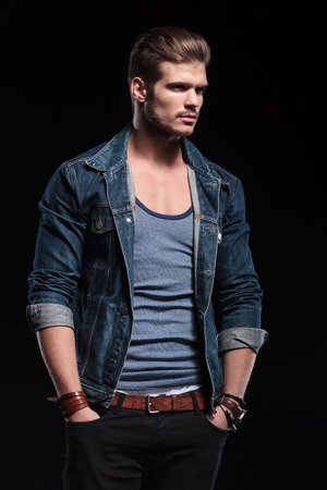 vogue style: side view of a young fashion man in casual jeans clothes looking away on dark background