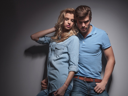 women and men: sexy casual couple , woman leaning against her boyfriend in studio