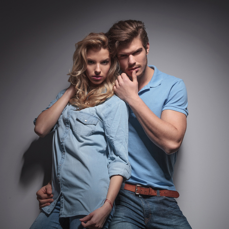provocative couple: sensual casual couple in a provocative pose , against gray studio wall