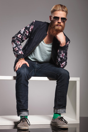 casual young man with a long red beard sitting like the thinker and looking into the camera. in a gray background studio photo